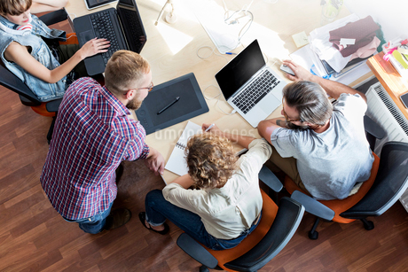 Overhead view design professionals working at laptops in meetingの写真素材 [FYI02176701]