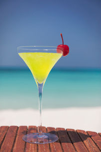 Yellow cocktail with cherry in martini glass on sunny tropical ocean beachの写真素材 [FYI02176729]