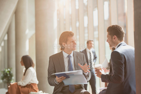 Businessmen discussing paperwork in sunny office lobbyの写真素材 [FYI02176758]