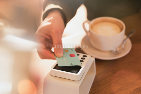 Close up man paying for cappuccino with credit card contactless payment in cafeの写真素材 [FYI02176763]