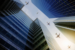 Airplanes flying in a row over highrise buildings, travel conceptの写真素材 [FYI02176772]