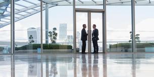 Businessmen talking in doorway of urban highrise buildingの写真素材 [FYI02176786]
