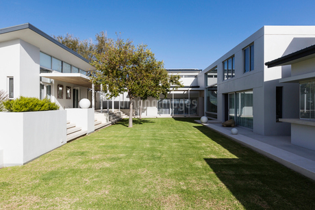Sunny modern luxury home showcase exterior with courtyardの写真素材 [FYI02176803]