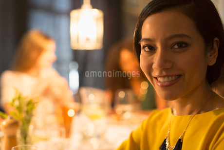 Close up portrait smiling woman dining with friends at restaurant tableの写真素材 [FYI02176827]