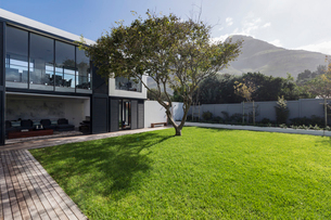Sunny home showcase exterior lawn and tree below mountainの写真素材 [FYI02176845]