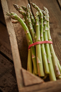 Still life close up fresh, organic, green, healthy asparagus bunch in wood crateの写真素材 [FYI02176873]