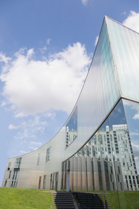 Modern building with reflection under sunny blue sky with cloudsの写真素材 [FYI02176876]