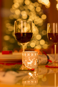 Red wine and Christmas candle on dining tableの写真素材 [FYI02176889]