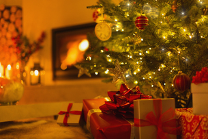 Gifts under Christmas tree in ambient living room with fireplaceの写真素材 [FYI02176890]