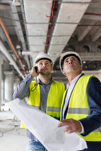 Male engineers with flashlight and blueprints looking up at construction siteの写真素材 [FYI02176896]