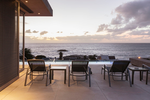 Lounge chairs on luxury patio with sunset ocean viewの写真素材 [FYI02176921]