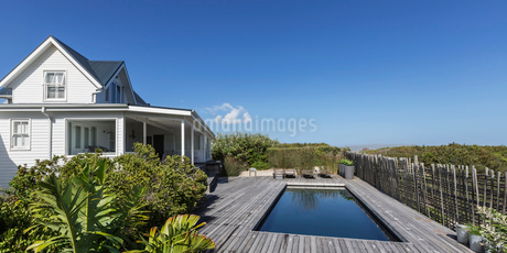 White home showcase exterior and swimming pool under sunny blue skyの写真素材 [FYI02176946]