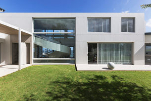 Sunny modern luxury home showcase exterior with grass courtyardの写真素材 [FYI02176951]