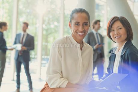 Portrait smiling businesswomen with digital tablet in office lobbyの写真素材 [FYI02176952]