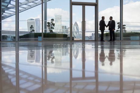 Businessmen handshaking in highrise office with urban city view, London, UKの写真素材 [FYI02176954]