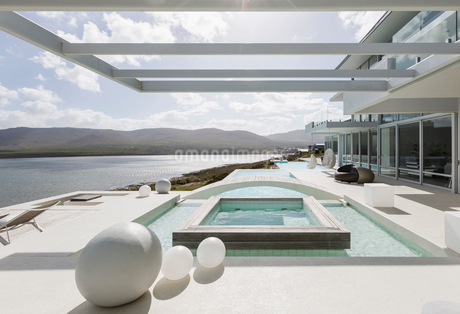 Sunny, tranquil modern luxury home showcase exterior with swimming pool and ocean viewの写真素材 [FYI02176961]