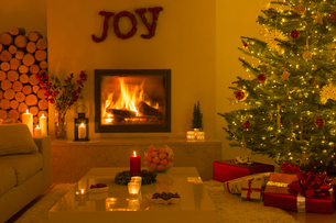 Ambient fireplace and candles in living room with Christmas treeの写真素材 [FYI02176970]