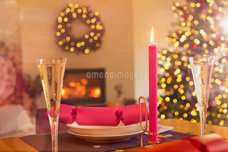 Champagne flute, candle and Christmas cracker on ambient tableの写真素材 [FYI02176984]