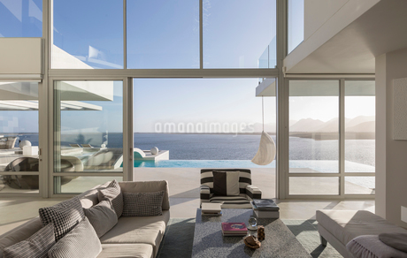 Sunny, tranquil modern luxury home showcase interior living room with patio and ocean viewの写真素材 [FYI02177002]