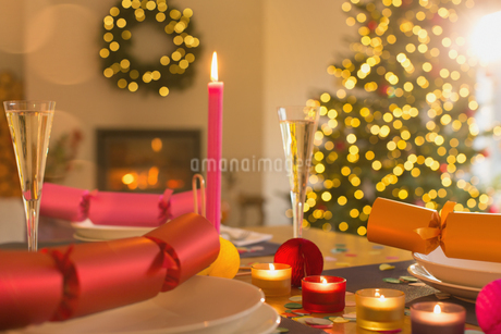 Candles, champagne and Christmas crackers on tableの写真素材 [FYI02177030]