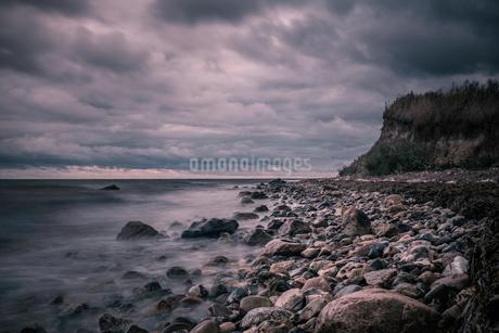 Tranquil rocks on ocean beach below stormy, overcast clouds, Bisserup, Denmarkの写真素材 [FYI02177072]