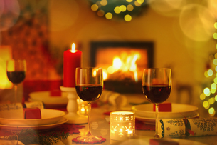 Red wine and candles on ambient Christmas table in front of fireplaceの写真素材 [FYI02177073]