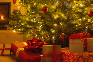 Gifts with red bows under illuminated Christmas treeの写真素材 [FYI02177094]