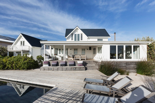Sunny white home showcase exterior with patio and swimming poolの写真素材 [FYI02177100]