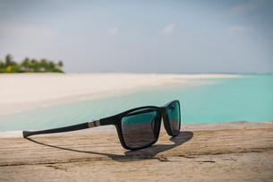 Close up sunglasses on sunny tropical beachの写真素材 [FYI02177133]