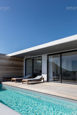Sunny modern luxury home showcase exterior patio and lap swimming poolの写真素材 [FYI02177141]