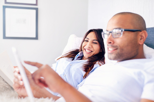 Smiling couple using digital tablet on bedの写真素材 [FYI02177148]