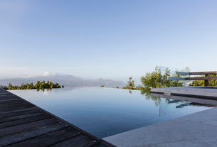 Tranquil luxury infinity pool with mountain view below blue skyの写真素材 [FYI02177164]