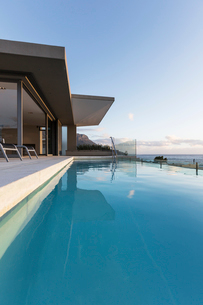 Tranquil blue lap swimming pool outside modern luxury home showcase exteriorの写真素材 [FYI02177184]