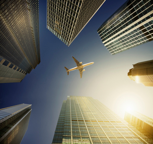 Airplane flying in blue sky over highrise buildings, travel conceptの写真素材 [FYI02177206]