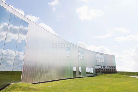Modern building with reflection and lawn under sunny blue sky with cloudsの写真素材 [FYI02177247]