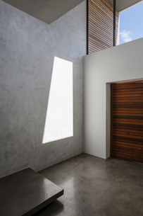 Sunshine casting reflection on modern, concrete home showcase interior wallの写真素材 [FYI02177254]