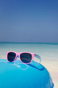 Pink sunglasses on blue inflatable ring on tropical oceanの写真素材 [FYI02177271]