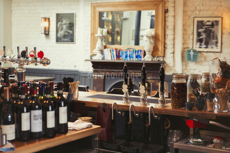 Wine bottles and tap handles behind bar in empty pubの写真素材 [FYI02177298]