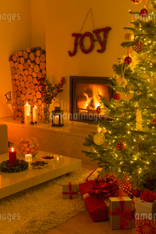 Ambient fireplace and candles illuminating living room with Christmas tree and decorationsの写真素材 [FYI02177348]