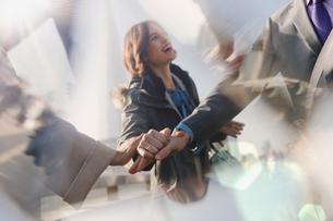 Smiling businesswoman behind handshaking business peopleの写真素材 [FYI02177362]