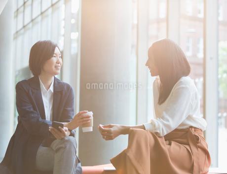 Businesswomen enjoying coffee break talking in sunny lobbyの写真素材 [FYI02177394]