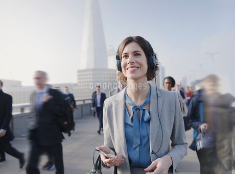 Smiling, confident businesswoman listening to music with smart phone and headphones on urban pedestrの写真素材 [FYI02177426]