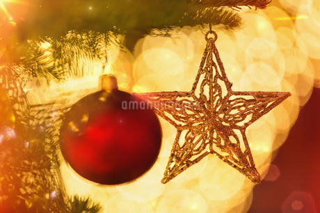 Close up red ornament and gold star hanging from branch of Christmas treeの写真素材 [FYI02177448]
