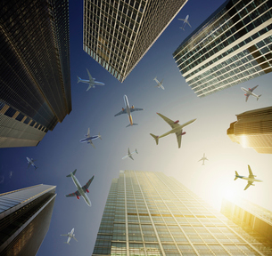 Airplanes in blue sky above highrise buildings, travel conceptの写真素材 [FYI02177451]