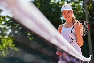 Portrait smiling young female tennis player holding tennis racket at netの写真素材 [FYI02177477]