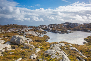 Sunny clouds over craggy rocks and water, Golden Road, Harris, Outer Hebridesの写真素材 [FYI02177486]