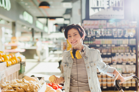 Portrait smiling, confident young woman with headphones grocery shopping in marketの写真素材 [FYI02177497]