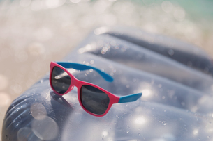 Close up pink and blue sunglasses on inflatable raft in sunny waterの写真素材 [FYI02177500]