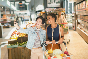 Smiling young lesbian couple taking selfie in grocery store marketの写真素材 [FYI02177525]