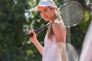 Portrait confident young female tennis player holding tennis racketの写真素材 [FYI02177532]